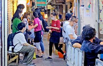 人々が集う栄町市場の飲食店街。4月1日からの時短要請への対応は店によって異なる=29日午後7時半、那覇市安里(金城健太撮影)