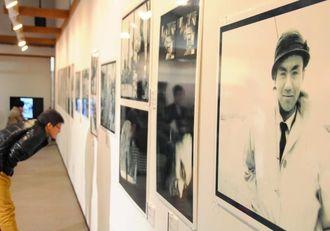 金城哲夫さんの足跡をたどる写真を熱心に見入る来場者=南風原文化センター