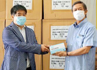 謝花喜一郎副知事(右)に医療用マスクなどを寄贈するブルースタイル沖縄の仲里信秀会長=11日、県庁