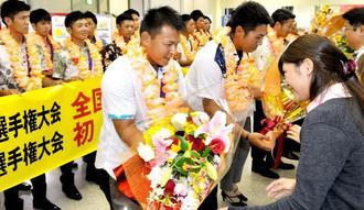 全日本クラブ選手権で優勝し祝福の花束を受け取る山根直樹主将(手前左)ら=那覇空港