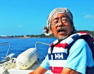 抗議船に乗り、大浦湾を見渡す魚住昭さん=4日、名護市