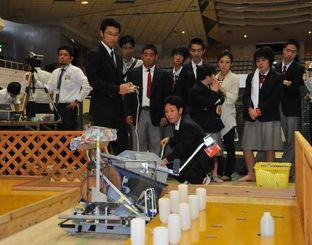 自作のロボットを操作して缶やペットボトルを拾う工業高校生=那覇市・県立武道館