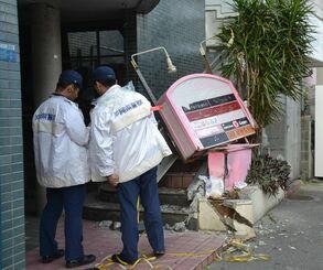 トラックが衝突した現場を調べる警察官ら=2019年4月4日、浦添市屋富祖のテナントビル前
