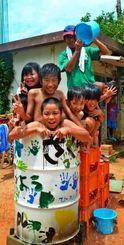 「竹とんぼ」こと森川武さん(右奥)にバケツで水をかけてもらいながら五右衛門風呂に入る子どもたち=15日、港川学童クラブ