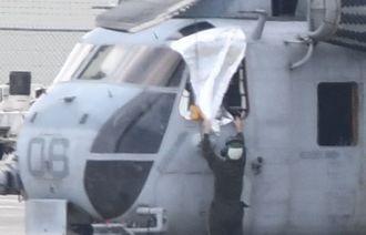 CH53E大型輸送ヘリの窓のない部分をシートで覆う作業員=13日午前11時52分、宜野湾市・米軍普天間飛行場(田嶋正雄撮影)