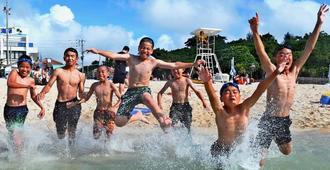 青空の下、海に飛び込む子どもたち=10日午後4時過ぎ、那覇市・波之上ビーチ(下地広也撮影)