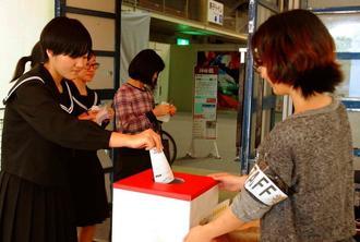 「みんなの1点賞」で気に入った作品に投票する参観者=24日、浦添市民体育館