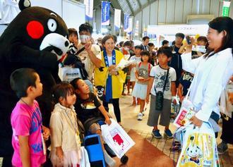 「沖縄旅フェスタ2017」でくまモンと記念撮影する子どもたち=11日、宜野湾市の沖縄コンベンションセンター