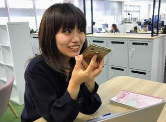 取材の合間を縫って、スマートフォンでニュースを吹き込む又吉さん=沖縄タイムス社