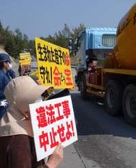 米軍キャンプ・シュワブから出てきた工事車両にプラカードを掲げて抗議する人々=19日、名護市辺野古