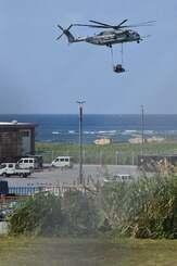 フォークリフトをつり下げてトリイ通信施設内に運搬する普天間飛行場所属のCH53E大型輸送ヘリ=27日午後1時38分、