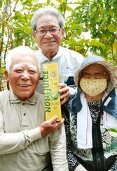 「護佐丸」をあしらったパッケージでノニのジュースを販売する海邦ファームの與那嶺安雄社長(中央)と生産農家の安里清一さん(左)、妻の艶子さん=9日、中城村伊舎堂