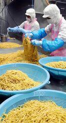 ゆでたての麺を冷ましながらほぐす作業員=29日、糸満市西崎町・サン食品