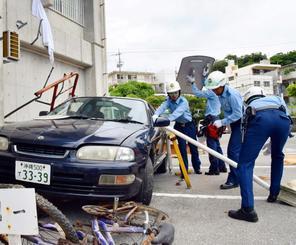 訓練で車内に閉じ込められた被災者を救助する署員ら=1日午前、浦添署