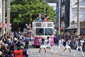 ひんぷんがじゅまる(後方)から名護大通りをパレードするミッキーマウスたち=24日