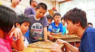 藤森哲也五段(右)と真剣な表情で将棋を指す児童ら=24日、本部小学校