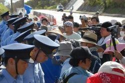 沖縄防衛局が敷いた鉄板の上から市民らを排除するため、一列になる警官隊。市民らとにらみ合いが続く=7月29日午後4時32分、名護市辺野古のキャンプ・シュワブゲート前