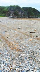 辺戸海岸の砂浜に残る四輪車の走行跡。奥の岩場に向けて続いている=2日