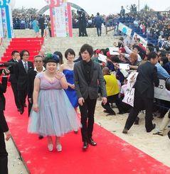 ファンの声援に包まれながらレッドカーペットを歩く渡辺直美さん(手前左)ら出演者=25日午後2時45分ごろ、宜野湾市・宜野湾海浜公園