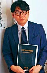 故翁長精一さんがまとめ、6月に出版予定の「旧天久村の民俗誌」を持つ孫の駿次さん=9日、那覇市天久の自宅