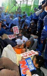 工事関係者の車両の進入を阻止しようとゲート前に座り込み、警察官に排除される市民ら=6日午前7時すぎ、名護市辺野古
