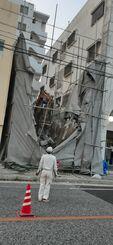 がれきが道路側に突き出る形で崩れかかったビルの解体工事現場=13日午後6時40分ごろ、那覇市若狭