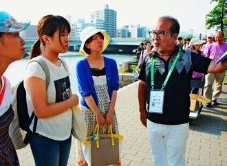 「核兵器がなくなることをみんなが待っているのに、平和の灯はまだ消えんのよ」と観光客に説明する座間味正彦さん(右)=6日午後、広島市・原爆ドーム