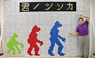 平面アート「君ノシンカ」と制作者の知念吉一さん(右)=伊江港旧ターミナル1階