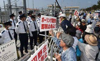 拘束者の解放を求め、県警に抗議の声を上げる人々=20日午前10時すぎ、名護市辺野古のキャンプ・シュワブゲート前