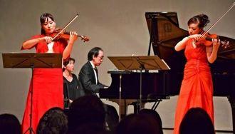 迫力ある音色で観客を魅了する神谷さん(手前左)と磯さん(同右)、新垣さん(後方)=13日、名護市民会館
