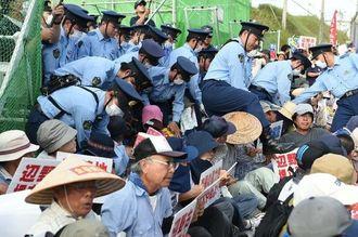 キャンプ・シュワブのゲート前で座り込みを続ける市民らを強制排除する警察官=3日午前7時すぎ、名護市辺野古
