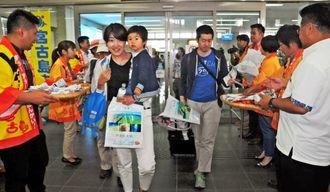 パンフレットや宮古島の特産品をもらい喜ぶ関西からの観光客=宮古空港