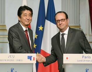 共同記者発表を終え、握手するフランスのオランド大統領(右)と安倍首相=20日、パリ(共同)