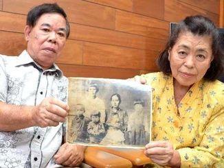 母ハルさんのたんすから見つかった眞栄平マツさん家族の写真をかざす宮城栄孝さん(左)、世志子さん夫妻=浦添市仲間