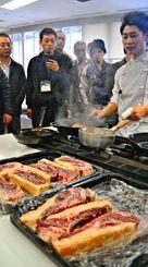 ドライエイジングした県産経産牛の調理方法を見学する試食会参加者=18日、那覇市の県男女共同参画センター「てぃるる」
