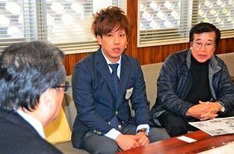 新垣村長(左)にアジア大会金メダルの報告をした安里秀策さん(中央)=北中城村役場