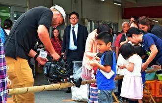 モズク流しイベントを楽しむ子どもたちを取材するグレート・ビッグ・ストーリーのカメラマンら=糸満市