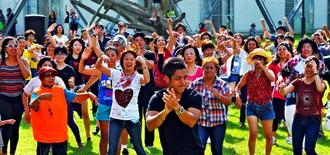 来場者を巻き込み、「サルサ」に合わせてダンスフラッシュモブを披露する県系人ら=日、沖縄セルラーパーク那覇(渡辺奈々撮影)