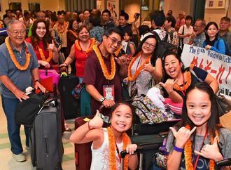 歓迎を受け、笑顔で到着を喜ぶハワイからの参加者=24日午後6時すぎ、那覇空港国際線ターミナル(渡辺奈々撮影)