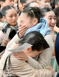 宝塚音楽学校の合格発表で、自分の番号を見つけて抱きあう受験生ら=28日午前、兵庫県宝塚市