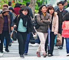 寒風が吹きすさぶ中、厚着で歩く人たち=5日午後5時半ごろ、那覇市久茂地(松田興平撮影)