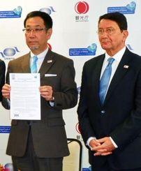 世界観光倫理憲章に署名した沖縄ツーリストの東良和会長。右は国連世界観光機関のタレブ・リファイ事務局長=25日午後、観光庁
