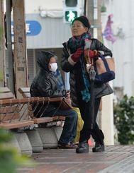 冷たい風に震えながらバスを待つ人たち=24日午前10時ごろ、那覇市の開南バス停