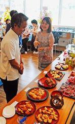 健康長寿復活に向けた拠点のオープンを祝う式典で招待客と懇談する伊是名カエさん(右端)=30日、読谷村大湾・シナジースクエア2階