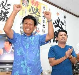 当確を決め、ガッツポーズで喜ぶ新崎進也さん(左)と弟の進悟さん=10日午前0時28分、那覇市長田の選対事務所