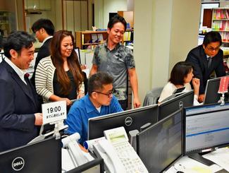 従業員のパソコンにはその日の退社予定時間が掲げられている。「この時間には帰るという自分自身とほかの従業員への宣言」と堀下和紀さん(左)=浦添市西洲、堀下社会保険労務士事務所