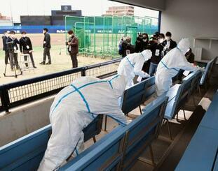 中日の2軍本拠地ナゴヤ球場で一塁側ベンチ内を消毒する防護服の作業員=30日午前、名古屋市