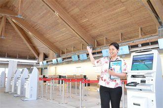 30日に開港する「みやこ下地島空港ターミナル」の搭乗受付口を紹介する下地島エアポートマネジメントのスタッフ=15日、宮古島市・同空港