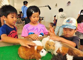モルモットの感触を楽しむ子どもたち=26日午後、那覇市おもろまちの県立博物館・美術館