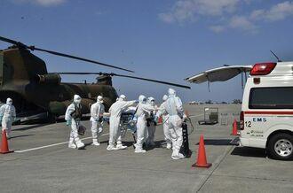ヘリで宮古島から輸送したコロナ患者を消防隊員に引き継ぐ自衛隊員=4日、那覇基地(陸上自衛隊第15旅団提供)